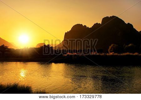 Sunset over Nam Song River with silhouetted rock formations in Vang Vieng Laos. Vang Vieng is a popular destination for adventure tourism in a limestone karst landscape.