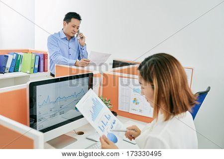 Entrepreneur reading business document when talking on phone