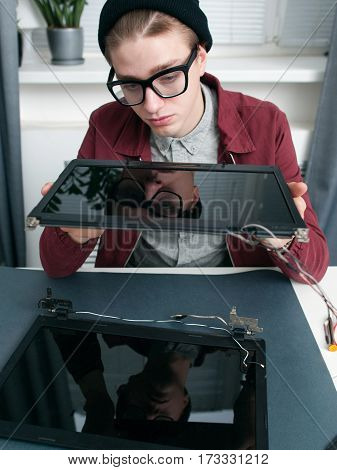 Expert examing new laptop monitors closeup. Young man looking at digital screen at office. Electronic production, repair workshop, modern technologies concept