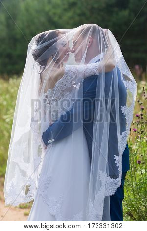 Happy bride and groom celebrating wedding day. Kissing married couple. Long family life concept