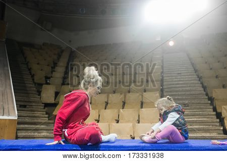 The future circus artist. Female gymnast sitting with his daughter at the barrier of the arena in the circus.
