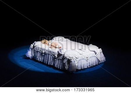 Beautiful blond woman in white dress lying on a white bed at the circus.