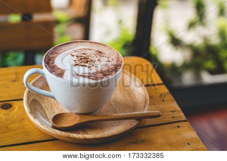 Coffee cup on the wooden table with faded theme
