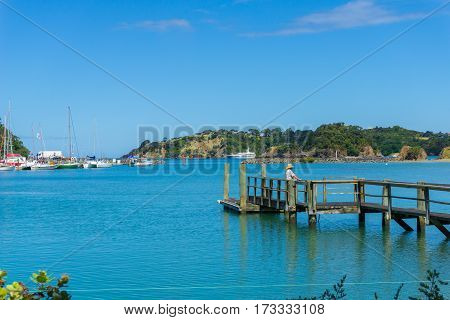Tutukaka, New Zealand - February 7, 2016; Jetty with man in straw hat projects into turquoise blue harbour surrounded by hills and boat filled marina.
