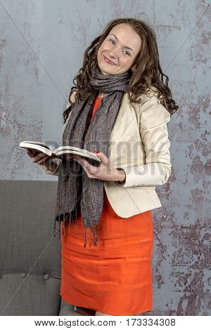 Young beautiful woman in a jacket and an office suit with a book