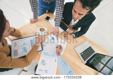 First person view of businessman explaining financial chart to coworkers