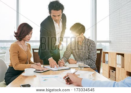 Financial manager explaining diagram to coworkers to meeting