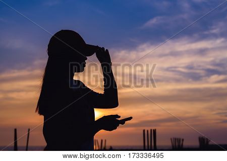 The girl use smartphone silhouette with sunset sky.