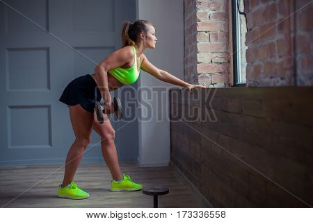 Beautiful young girl is training with a barbell at fitness. She is weating green top and black shorts.