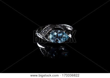 Silver Ring With Blue Topaz Isolated On A Black Background.