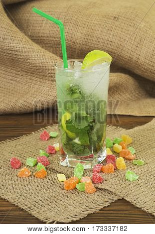 Fresh drink lemonade mojito in a glass on wooden background. Alcohol cocktails with Rum, lime, mint, ice cubes and brown sugar closeup.