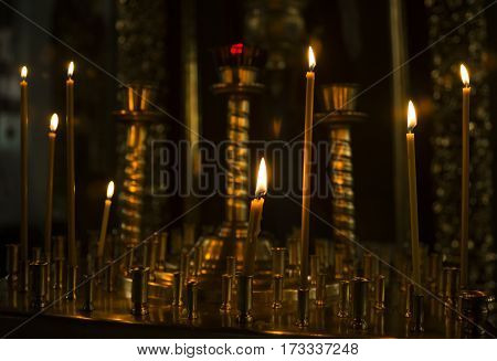 sacred burning candles in the church. Church candles background. Selective focus