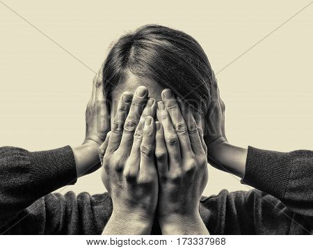 Concept of fear domestic violence. Woman's hands covers her face and ears. Black and white toned.