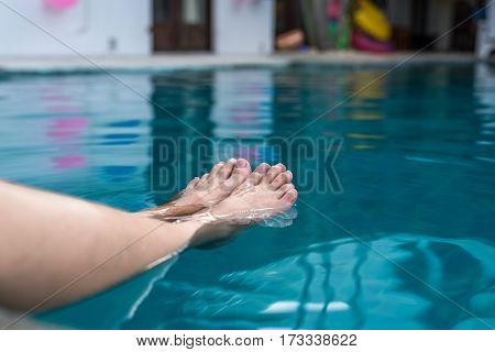 The girl dipping feets in the pool