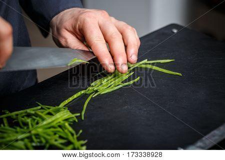 Chef cutting green peas on the black cutting board