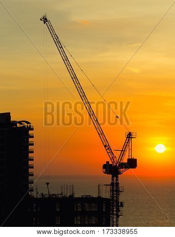 Silhouette of construction tower crane with sunset background at evening time.