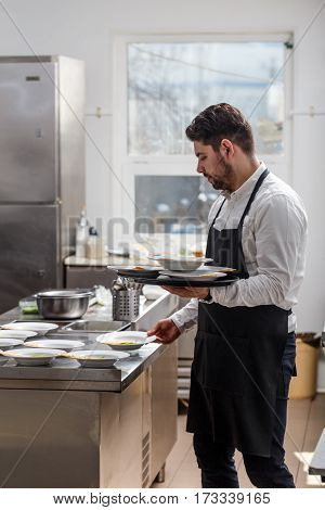 Young waiter wearing apron ready to serve lunch