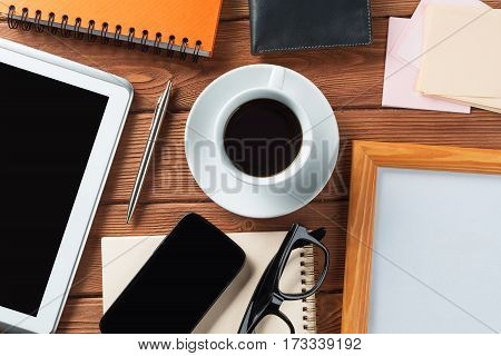 Still life photo of tablet notepad coffee glasses and other stuff on wooden table