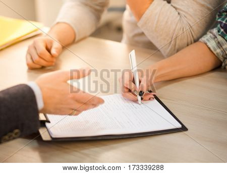 Closeup toned of woman signing agreement or contract in office interior. Salesman offering contract for purchase or sale. Apartment. Flat. Automobile.