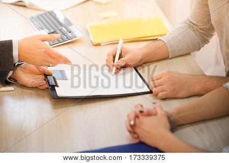 Closeup toned of man signing agreement or contract for getting new credit card represented by salesman or businessman. Contract for buying apartment, flat, car.