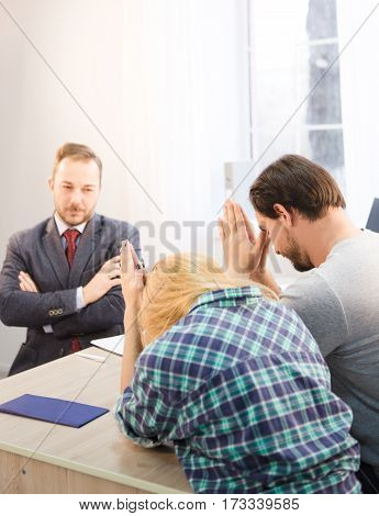 Toned of young couple communicating with bank officer and begging him to give them credit card for buying new apartment, flat, car. Dealership concept.