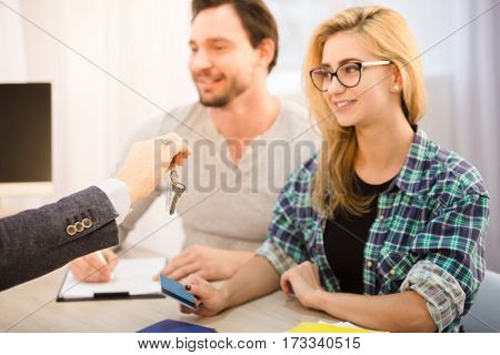 Toned of young businessman giving key to happy smiling young couple. Happy lady holding credit card and smiling after signing agreement or contract for purchase or sale.