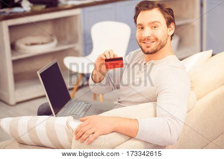 Toned of handsome man smiling and showing credit card to camera while sitting on sofa or couch and working on laptop computer at home. Freelance concept. Money concept.