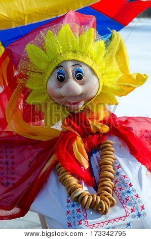 Pancake doll in colorful dress with bunch of bagels on neck