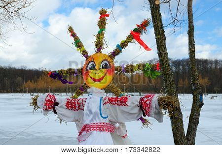 Shrovetide doll with face as sun and straw braids in form of sun rays on background of spring landscape