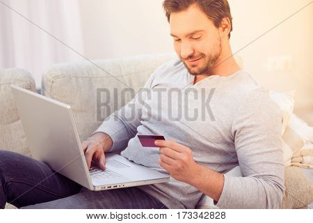 Toned of handsome man sitting on sofa and working on laptop computer. Bearded man looking at credit card and smiling. Freelance concept. Business concept.
