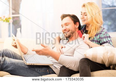 Toned of happy couple looking at laptop computer's screen and smiling. Blond lady holding credit card after signing agreement or contract for purchase or sale.