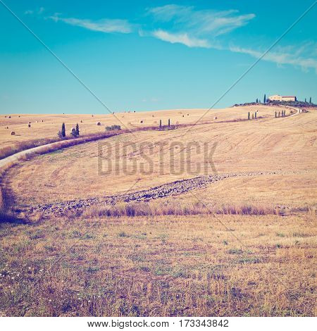 Dirt Road Leading to the Farmhouse across the Fields with Many Hay Bales in Tuscany Italy Instagram Effect