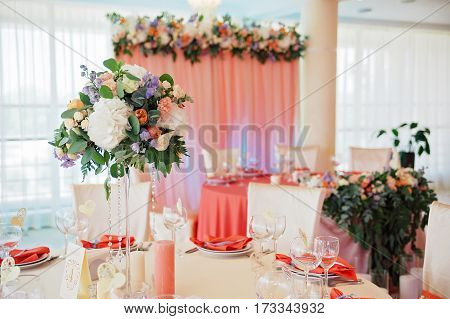 Wedding guest numbered table, decorated with bouquet and settings, in biege and peachy colours