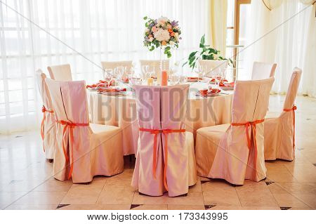 Wedding guest numbered table, decorated with bouquet and settings, decorated with cloth and bows chairs, in biege and peachy colours