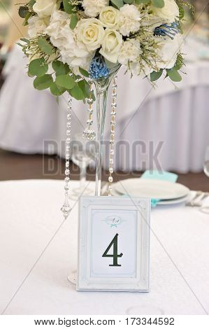 Guest wedding table with number and bouquet, closeup