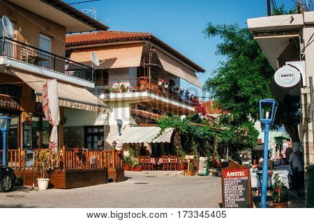 Afitos Halkidiki Greece - May 24 2015: Typical buildings on the central square with cafes and restaurants in Greek resort of Afitos on Kasandra penisula Halkidiki Greece
