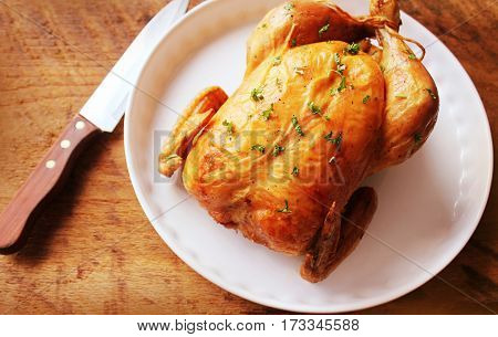 Roasted chicken on wooden background. Top view.