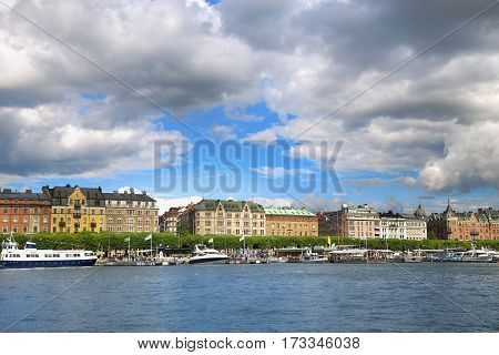 STOCKHOLM SWEDEN - AUGUST 20 2016: Many people walk and visit on Strandvagen street on Ostermalm distric with touristic sightseeing boats in Stockholm Sweden on August 20 2016.