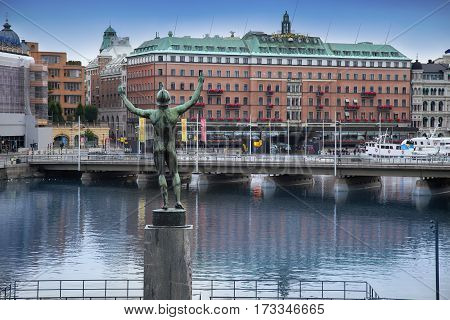 STOCKHOLM SWEDEN - AUGUST 20 2016: View of luxury hotel Grand Hotel at Stockholm waterfront and Sun Singer Statue at Stromparterren Park from Norrbro in Stockholm Sweden on August 20 2016.