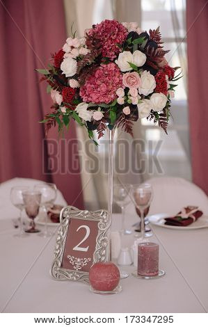Wedding guest numbered table, decorated with bouquet and settings, in biege and dark red colours