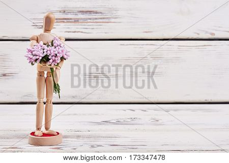 Manikin on wooden background. Invite her for a date.