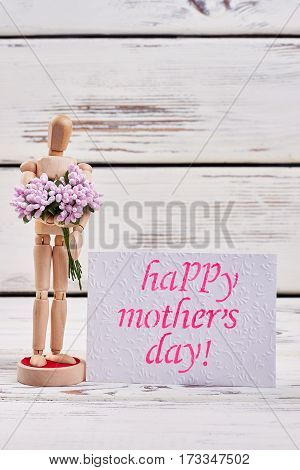 Wooden man and pink flowers. For dear mother.