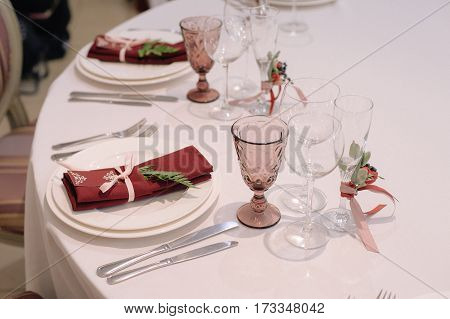 Decorated with flowers boutonniere wine and champagne glasses and settings with decorated napkin