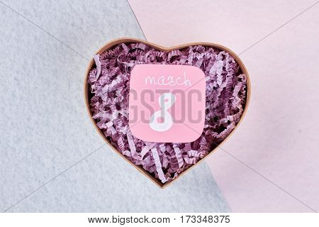 Greeting card and heart-shaped box. Best wishes on 8 of March.