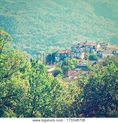 Medieval Italian City on a Hilltop Surrounded by Mountains Covered with Forests Instagram Effect