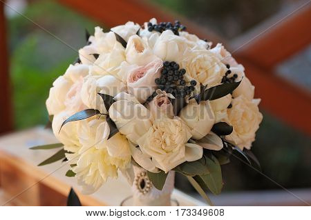 Beautifully decorated bouquet of white and pink roses, peons, petals, berries and green petals