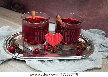 two glasses of mulled wine with cherries cinnamon and star anise for lovers on silver vintage tray with red heart. concept for a romantic anniversary Valentine's day