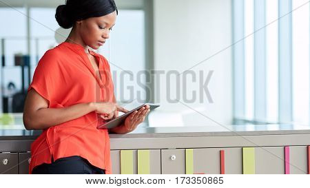 Attractive businesswoman wearing a bright orange blouse while looking at the screen of the digital electronic tablet that she is busy using with large bright windows in the background.