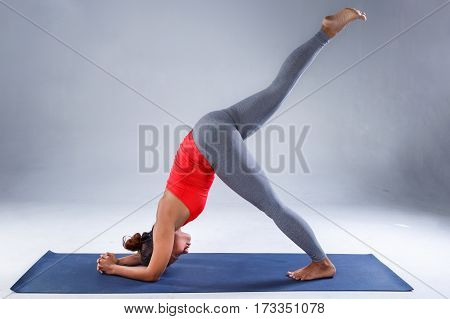 Yoga concept, Pretty sporty indian woman practicing difficult yoga pose in a concrete background, Sport healthy concept