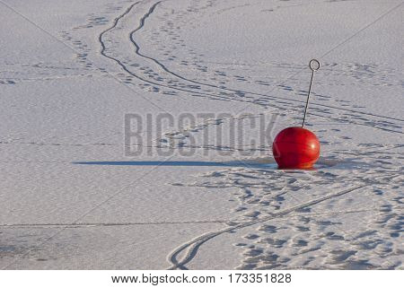 Buoy in frozen lake in winter, nature background